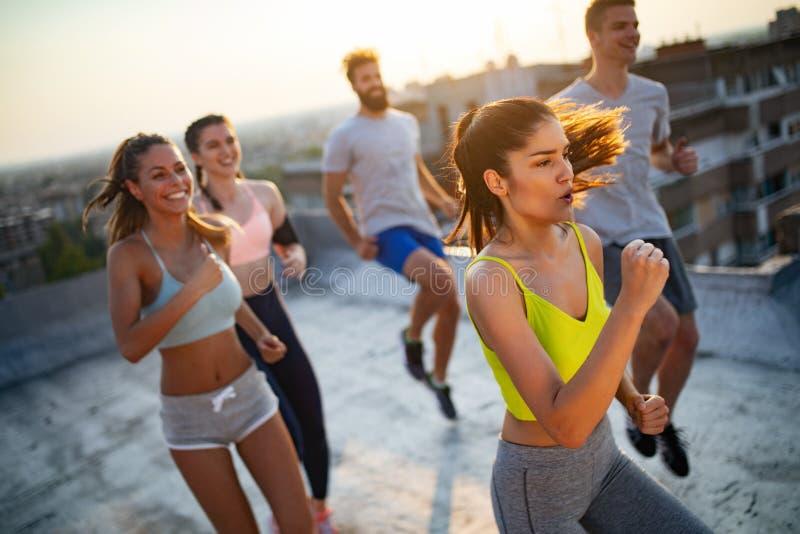 Groep jonge gelukkige mensenvrienden die in openlucht bij zonsondergang uitoefenen royalty-vrije stock fotografie