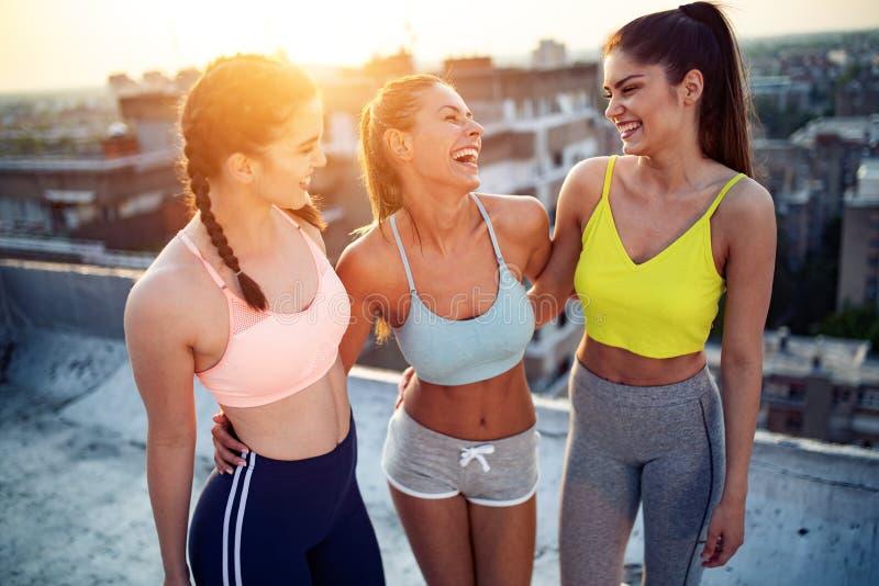 Groep jonge gelukkige mensenvrienden die in openlucht bij zonsondergang uitoefenen stock afbeelding