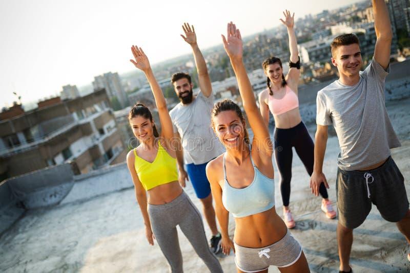 Groep jonge gelukkige mensenvrienden die in openlucht bij zonsondergang uitoefenen royalty-vrije stock foto