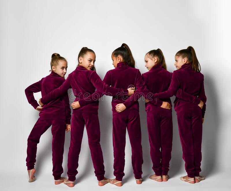 Groep jonge lachende meisjes gymnasten in donkerrode fluwelen sportkostuums die achteruit staan en elkaar omarmen stock afbeeldingen