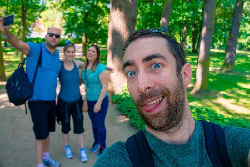 Groep jonge mannen en vrouw die een selfiebeeld met een smartphone of camera nemen bij het park stock foto's