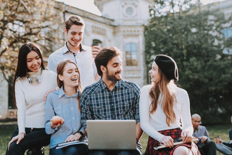 Groep jonge mensen zit binnenplaats universiteit royalty-vrije stock afbeeldingen