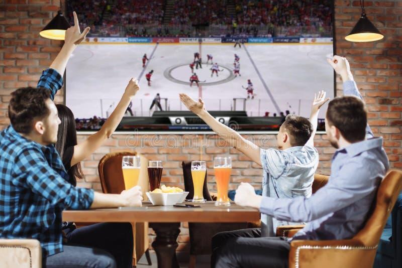 Groep jonge mooie vrienden die op TV letten en voor hun team toejuichen terwijl het rusten in bar stock afbeeldingen