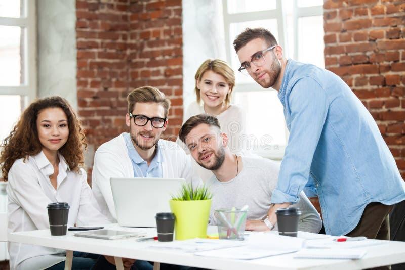 Groep jonge multiraciale mensen die in modern licht bureau werken Zakenlieden aan het werk tijdens vergadering stock foto's