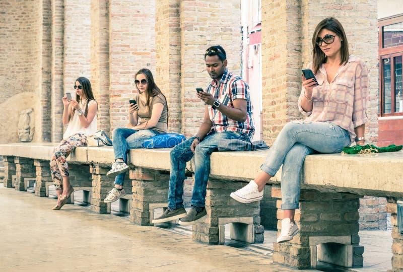 Groep jonge multiraciale vrienden die smartphone gebruiken