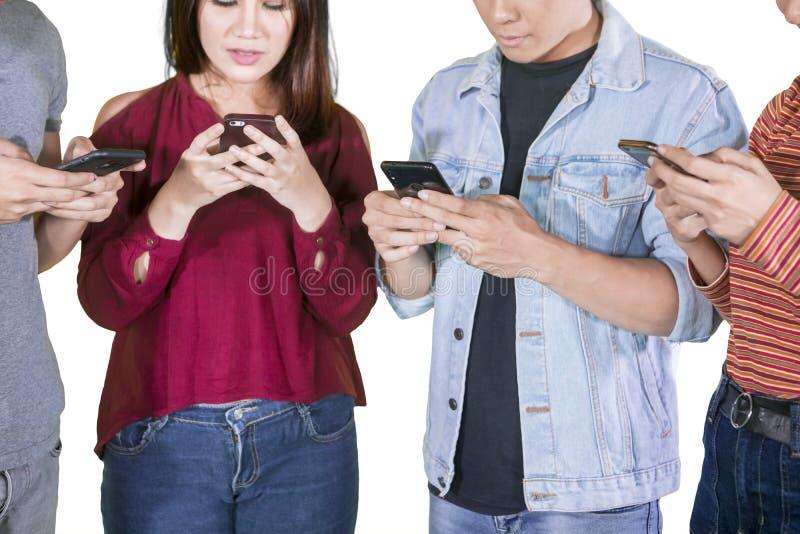 Groep jonge onbekende mensen die telefoons met behulp van stock afbeelding