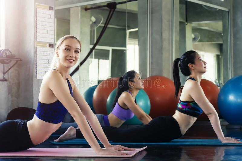 Groep jonge sportieve aantrekkelijke mensen die yogales uitoefenen stock afbeelding