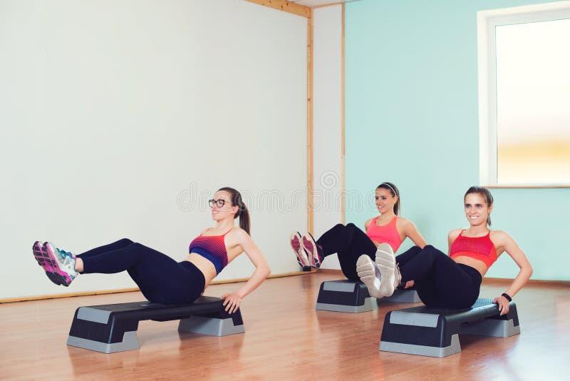 Groep jonge sportvrouwen die met steppers in gymnastiek uitwerken stock afbeeldingen