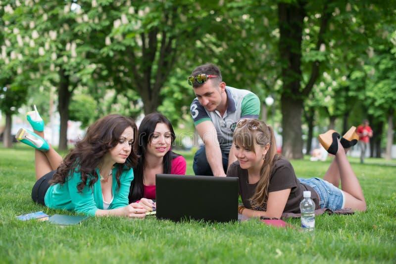 Groep jonge student die laptop samen met behulp van royalty-vrije stock afbeeldingen