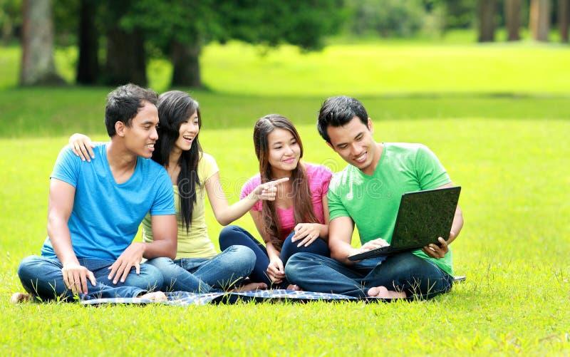 Groep jonge student die openlucht laptop met behulp van stock fotografie