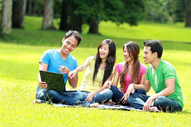 Groep jonge student die openlucht laptop met behulp van stock afbeeldingen
