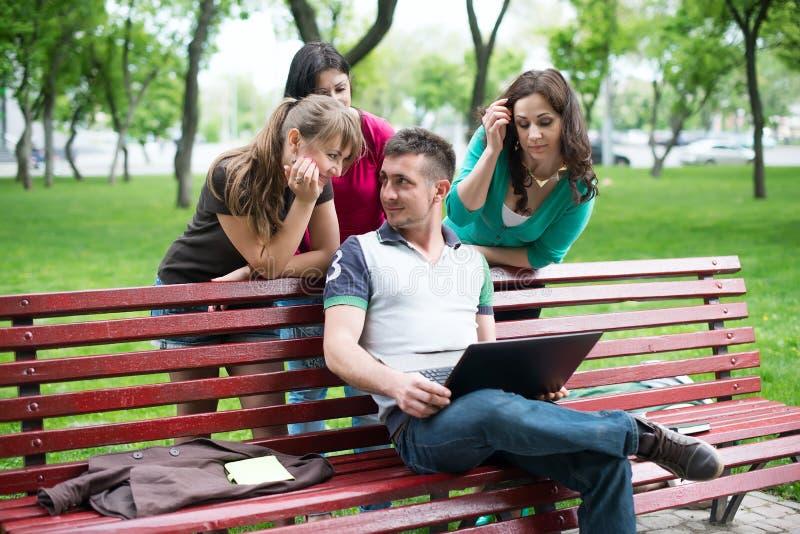 Groep jonge studenten die laptop met behulp van stock foto