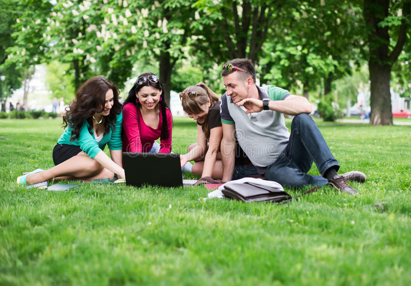 Groep jonge studenten die op gras zitten stock afbeelding