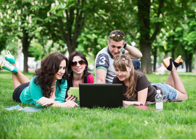 Groep jonge studenten die op gras zitten royalty-vrije stock foto's