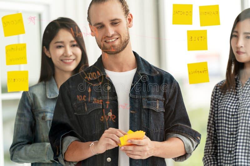Groep jonge succesvolle creatieve multi-etnische teamglimlach en uitwisseling van ideeën op project op kantoor stock fotografie