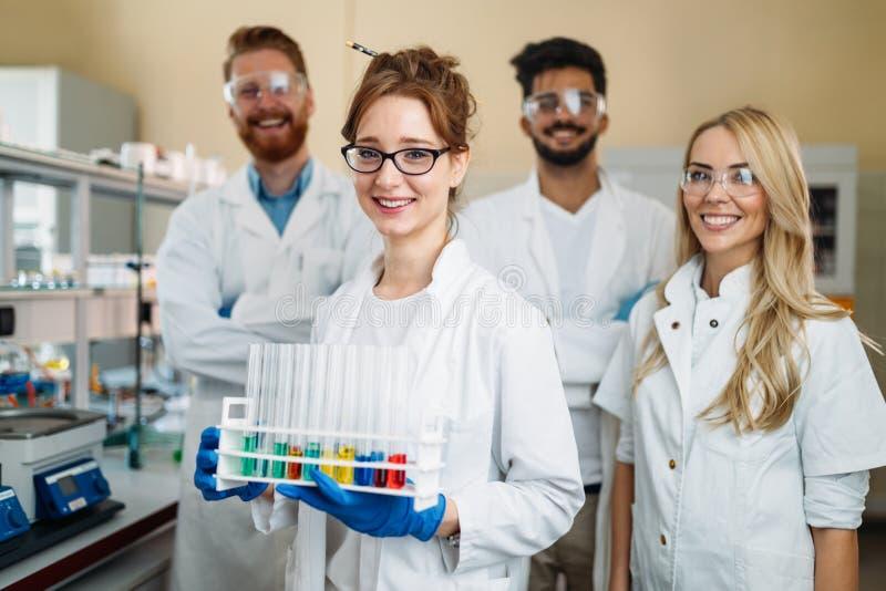 Groep jonge succesvolle wetenschappers die voor camera stellen stock fotografie