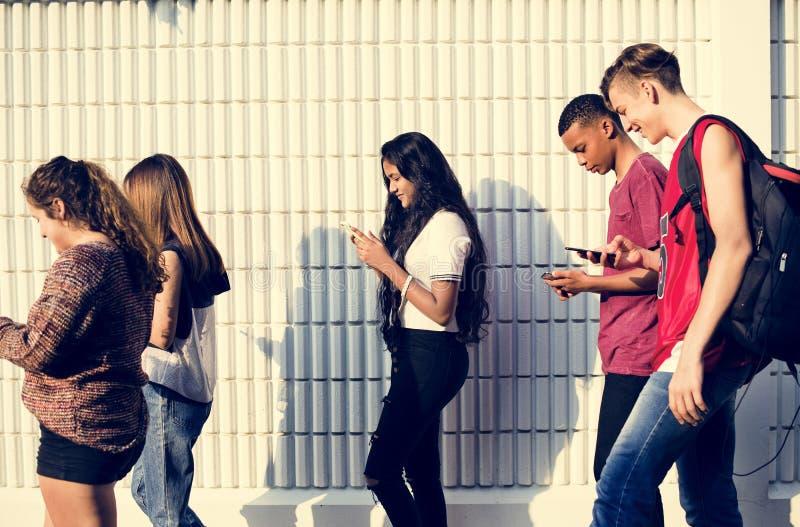 Groep jonge tienervrienden die naar huis na school het gebruiken lopen royalty-vrije stock fotografie