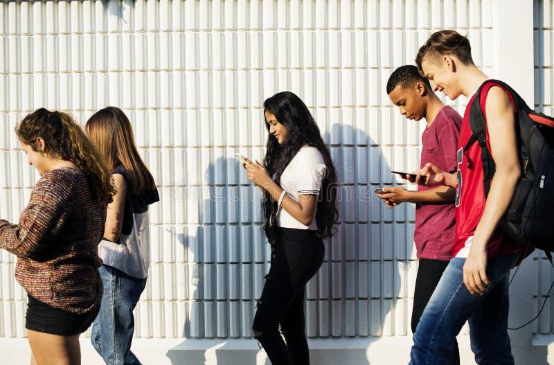 Groep jonge tienervrienden die naar huis na school lopen stock afbeeldingen