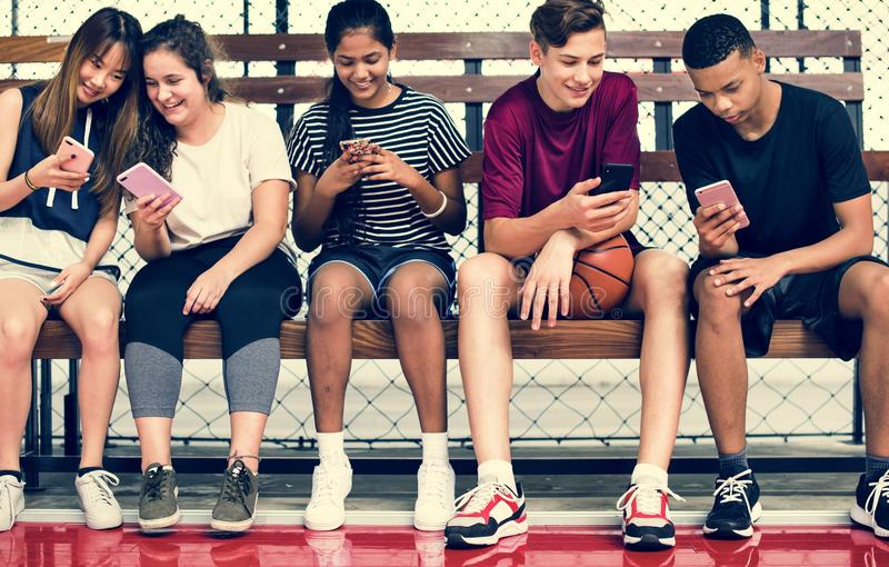 Groep jonge tienervrienden op een basketbalhof die gebruikend smartphone ontspannen stock afbeeldingen
