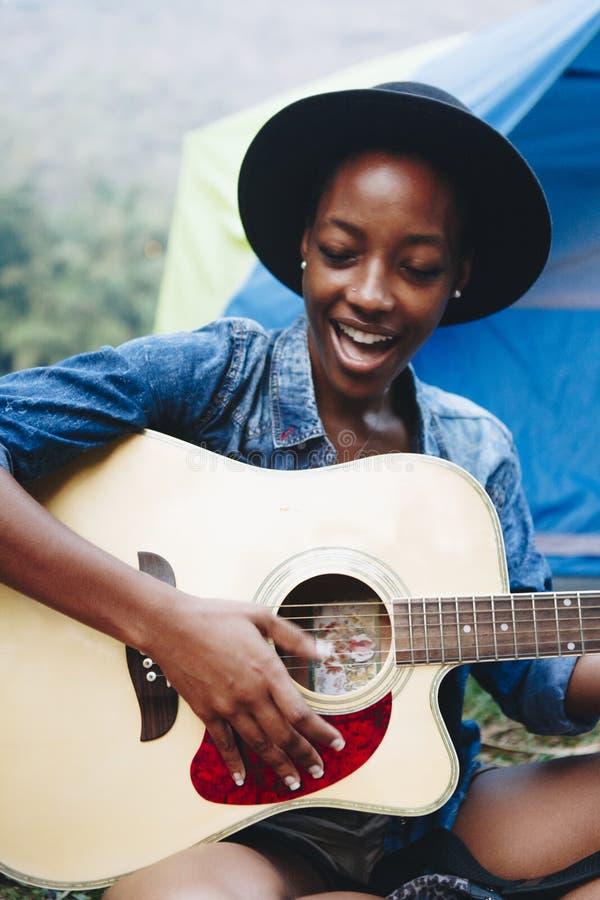Groep jonge volwassen vrienden in kampeerterrein het spelen gitaar royalty-vrije stock afbeeldingen
