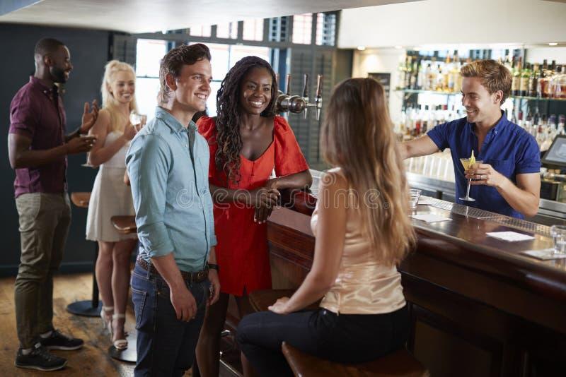 Groep Jonge Vrienden die in Bar ontspannen die zich bij Teller bevinden stock fotografie
