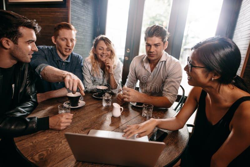 Groep jonge vrienden die bij koffie met laptop zitten stock afbeeldingen