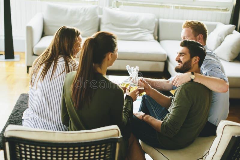 Groep jonge vrienden die cider drinken en pret in ruimte hebben stock afbeelding