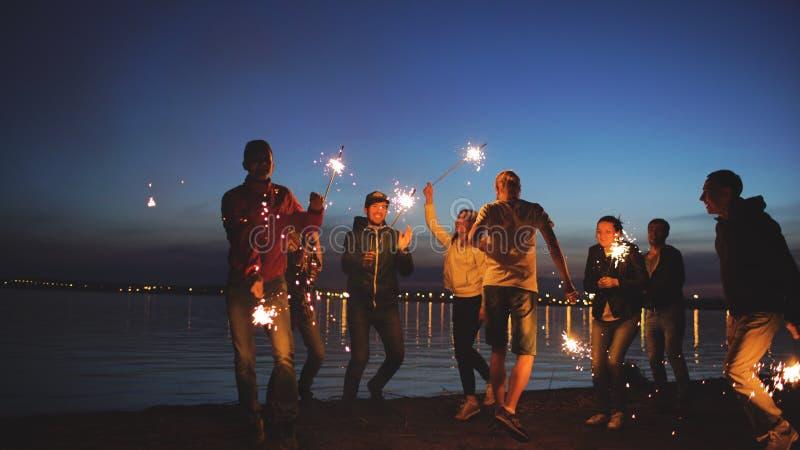 Groep jonge vrienden die een strandpartij hebben Vrienden die en met sterretjes in schemeringzonsondergang dansen vieren stock foto