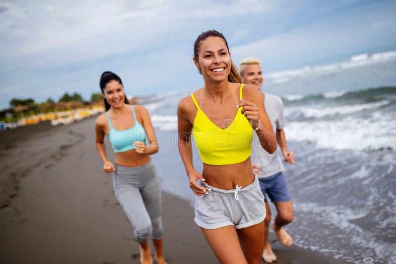 Groep jonge vrienden die en op het strand lopen uitoefenen stock afbeeldingen