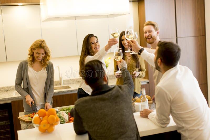 Groep jonge vrienden die met witte wijn roosteren stock foto's