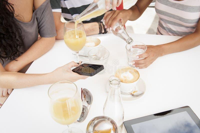 Groep jonge vrienden die samen uit het genieten van een van koffie hangen stock foto's