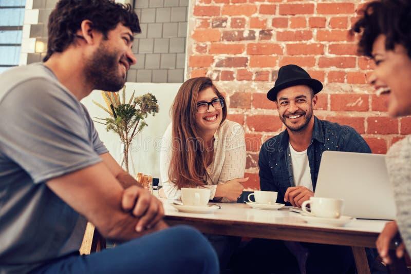 Groep jonge vrienden die uit bij een koffie hangen royalty-vrije stock afbeelding