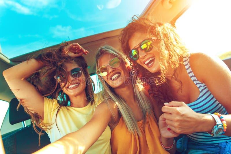 Groep jonge vrienden die van een dag genieten bij het meer Drie het vrouwelijke vrienden genieten die in de auto reizen royalty-vrije stock foto's