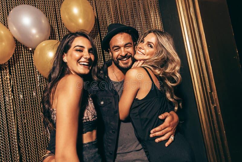 Groep jonge vrienden in een partij bij nachtclub royalty-vrije stock afbeeldingen