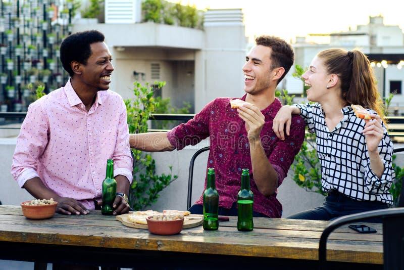 Groep jonge vrienden met pizza en flessen van drank royalty-vrije stock afbeeldingen