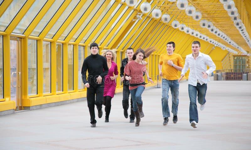 Groep jonge vriendenlooppas op voetgangersbrug royalty-vrije stock foto's