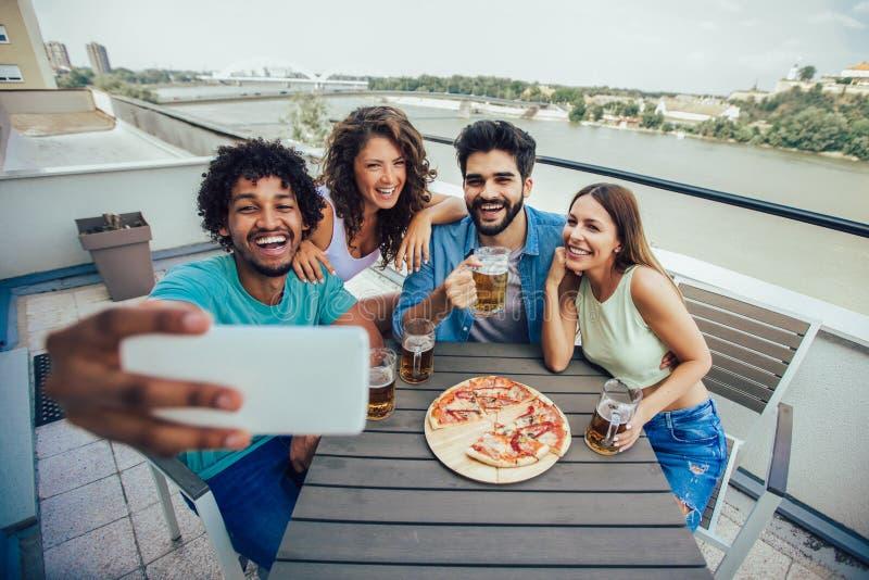 Groep jonge vrolijke mensen die pizza eten en bier drinken terwijl het zitten bij het kinderspel op het dak stock afbeelding