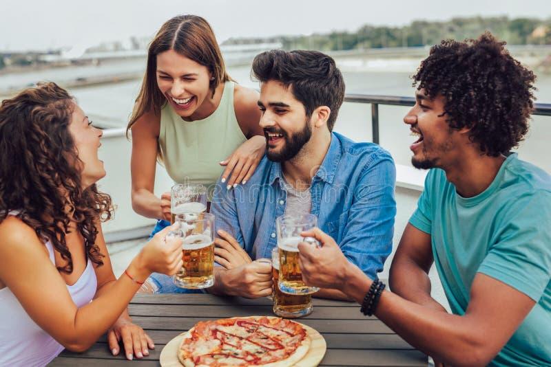 Groep jonge vrolijke mensen die pizza eten en bier drinken terwijl het zitten bij het kinderspel op het dak stock afbeeldingen