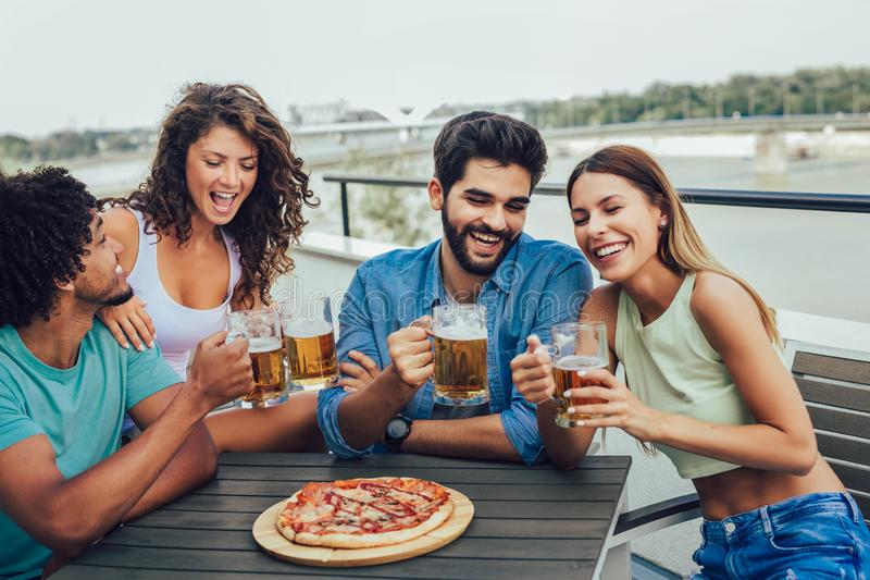 Groep jonge vrolijke mensen die pizza eten en bier drinken terwijl het zitten bij het kinderspel op het dak royalty-vrije stock foto's