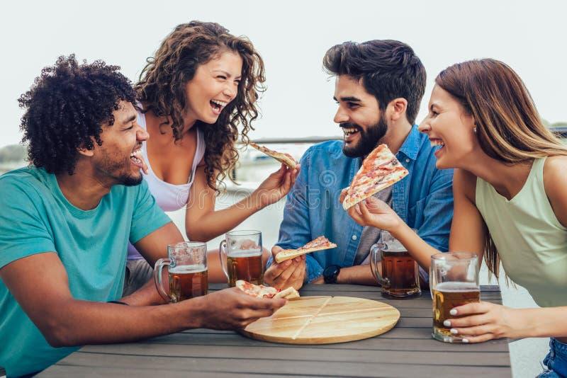 Groep jonge vrolijke mensen die pizza eten en bier drinken terwijl het zitten bij het kinderspel op het dak royalty-vrije stock fotografie