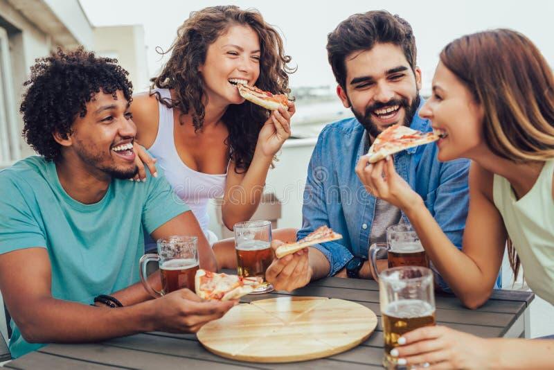 Groep jonge vrolijke mensen die pizza eten en bier drinken terwijl het zitten bij het kinderspel op het dak stock foto's