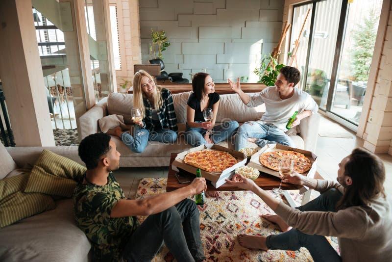 Groep jonge vrolijke vrienden die uit samen thuis hangen stock afbeeldingen