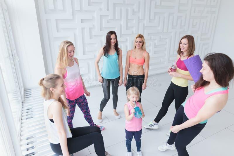 Groep jonge vrouwen met een babymeisje die een praatje na een klasse van de geschiktheidsdans hebben stock afbeeldingen