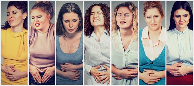 Groep jonge vrouwen met handen op maag die slechte pijnenpijn hebben stock afbeelding