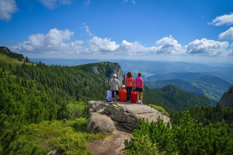 Groep jonge wandelaars die op een klippenrand zitten in de Ceahlau-bergen in Roemenië stock afbeelding