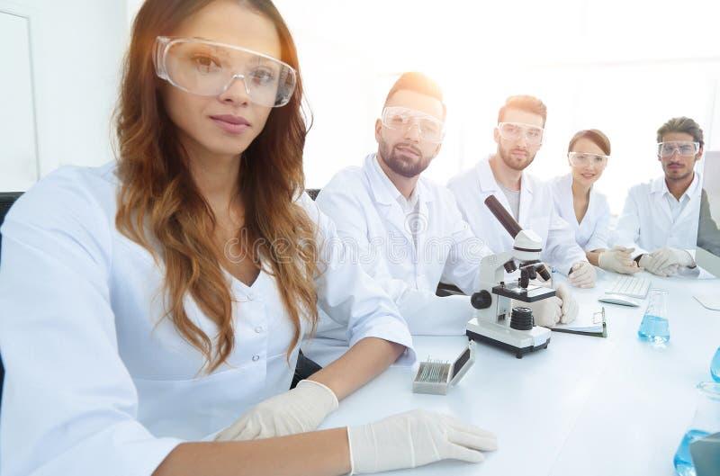 Groep jonge werkers uit de gezondheidszorgproefneming in onderzoeklaboratorium stock foto's