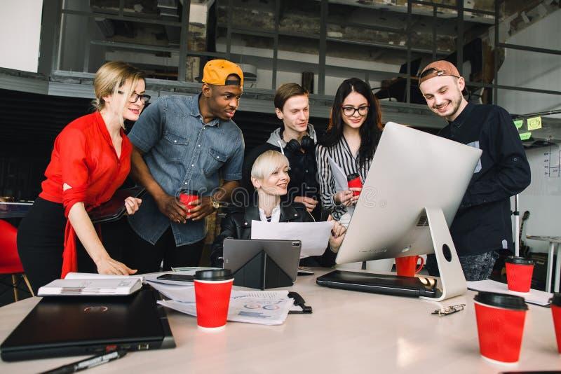 Groep jonge zes bedrijfsmensen en softwareontwikkelaars in toevallige uitrusting die als groep in zolderbureau werkt stock foto