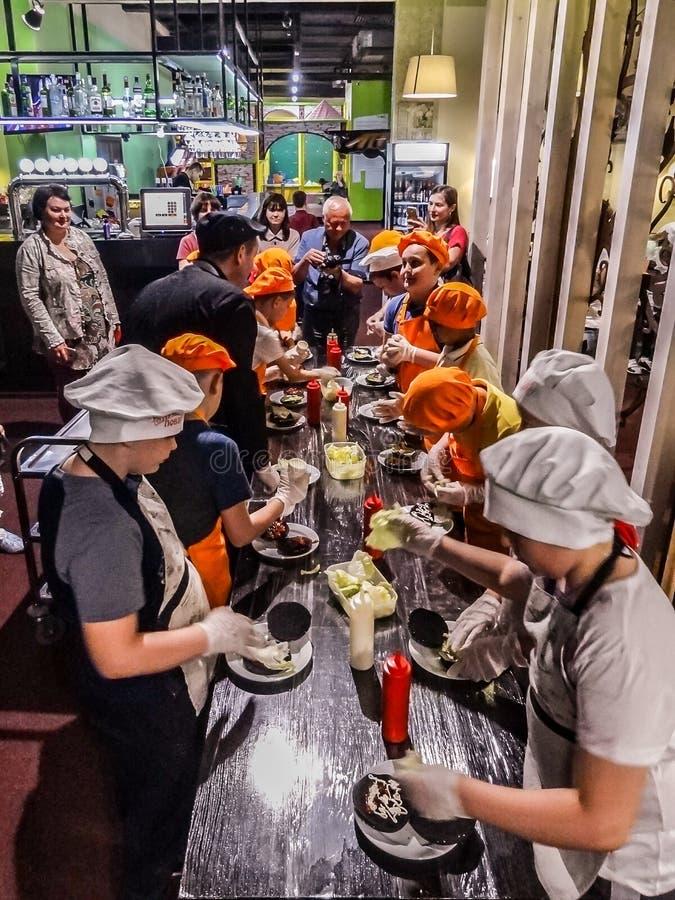 Groep jongens en meisjes door lijst het koken burgers Hoofdklasse over het koken van snel voedsel stock afbeeldingen
