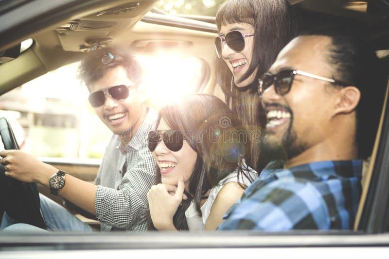 Groep jongeren die in auto glimlachen stock foto