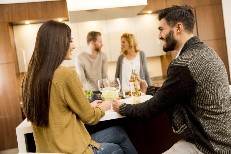 Groep jongeren die diner hebben en wijn in modern drinken royalty-vrije stock foto's